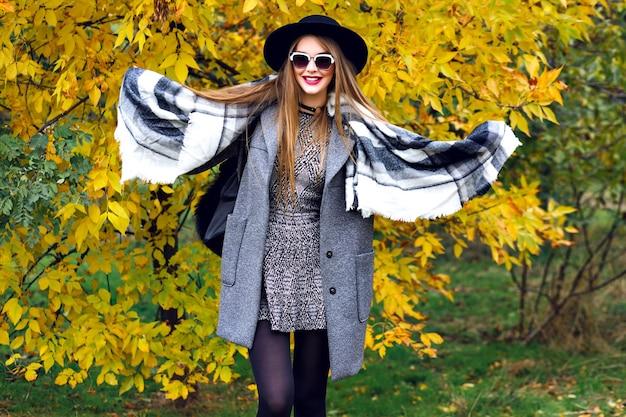 Ritratto di moda autunnale della splendida modella elegante in posa al parco, foglie dorate e clima fresco, abiti di lusso in stile street, trucco luminoso, grande sciarpa, mini abito sopra cappotto e cappello vintage.