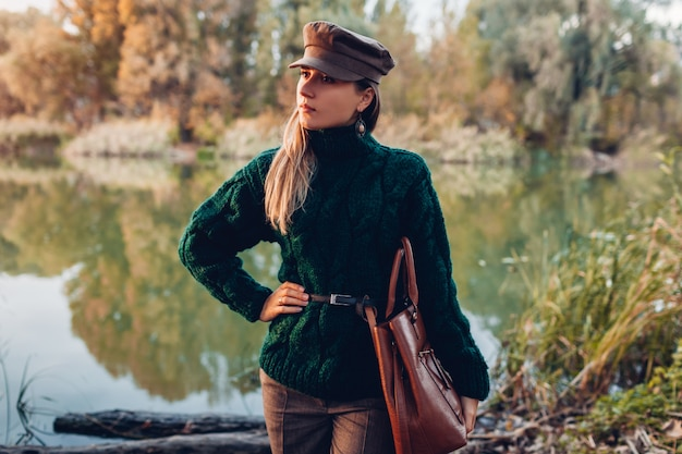 Autumn fashion. young woman wearing stylish outfit and holding handbag outdoors. clothing and accessories