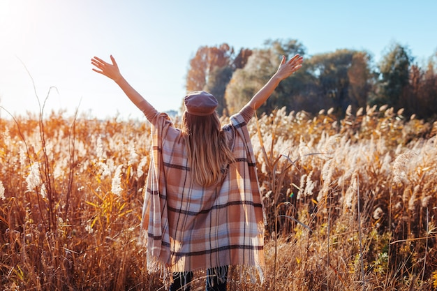 Autumn fashion. young woman wearing stylish poncho outdoors. clothing and accessories. happy girl raising hands