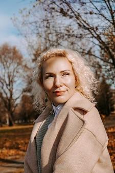 Осенняя модная красивая блондинка женщина в солнечный день