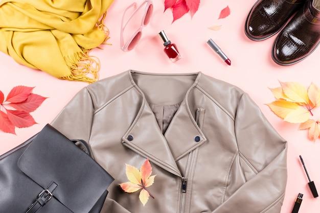 葉とピンクのテーブルの上の秋の女性服