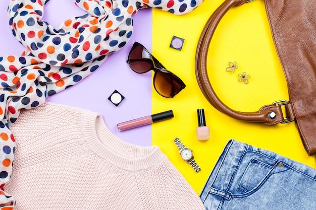 秋の女性服-ピンクのセーター、ブルージーンズ、革製のハンドバッグ、プリントスカーフ、アクセサリー、メイクアップ製品