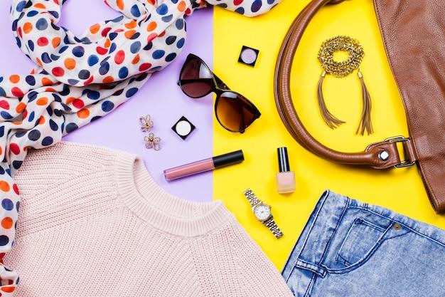秋の女性服-ピンクのセーター、ブルージーンズ、革のハンドバッグ、プリントスカーフ、アクセサリー、メイクアップ製品