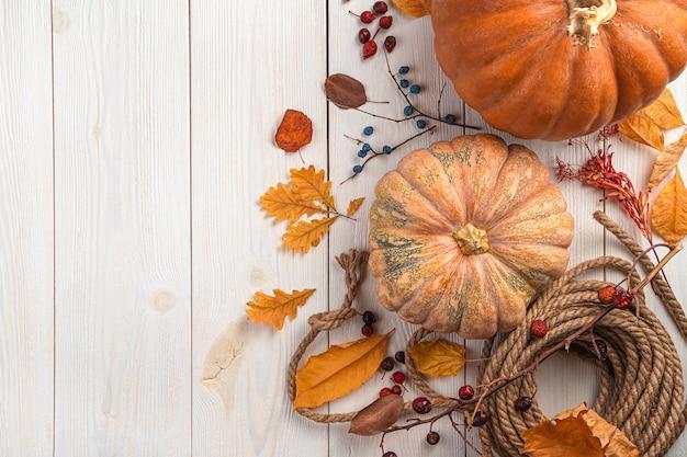Осенний праздничный фон с ягодами тыквы и листвой на белом деревянном фоне