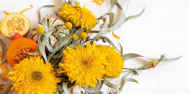 白い背景のクローズアップに花とカボチャと秋のお祭りの構成。