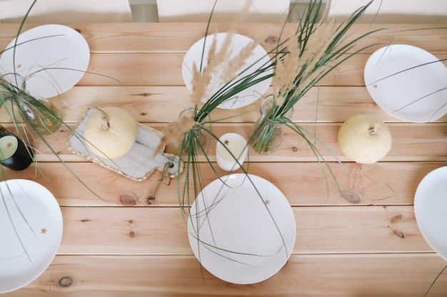 Осеннее праздничное украшение стола тарелками с белыми тыквами и свечами на деревянном столе