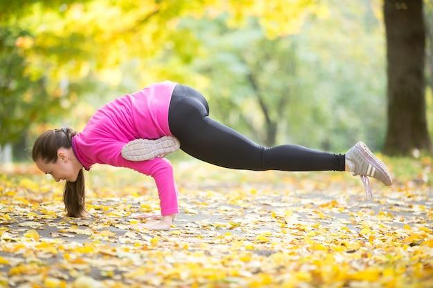 Autumn fitness outdoors: eka pada galavasana pose
