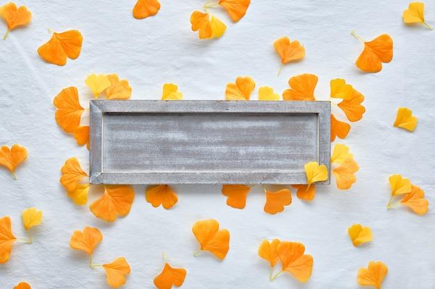 秋のフラットは、オレンジと茶色の背景を置きます。散乱のオレンジ色のイチョウの葉と白い繊維の背景にコピースペースを持つ空白の木製ボード。