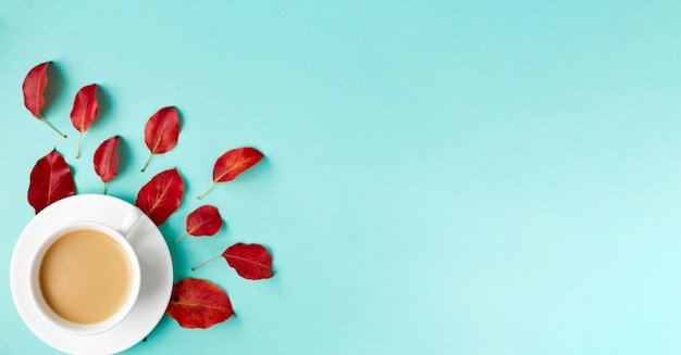 Осенняя квартира лежит фон на синем. композиция с реалистичными красными листьями и чашкой кофе. привет, октябрьская концепция. копировать пространство