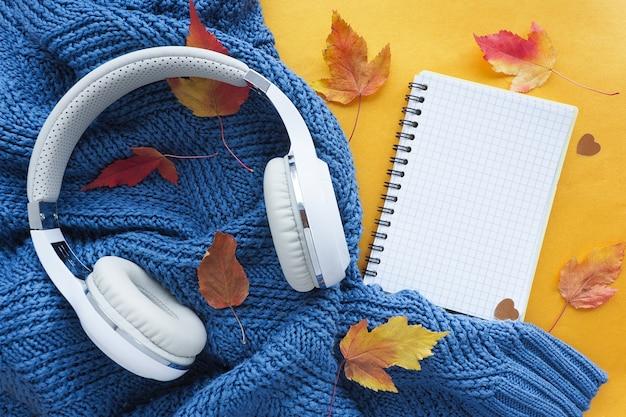 秋のフラットレイ。青いニットのセーター、赤と黄色のカエデの葉、ヘッドフォン、開いたノートブック。