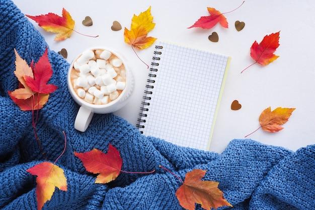 秋のフラットレイ。青いニットのセーター、赤と黄色のカエデの葉、開いたノートブック、マシュマロ入りのコーヒー。