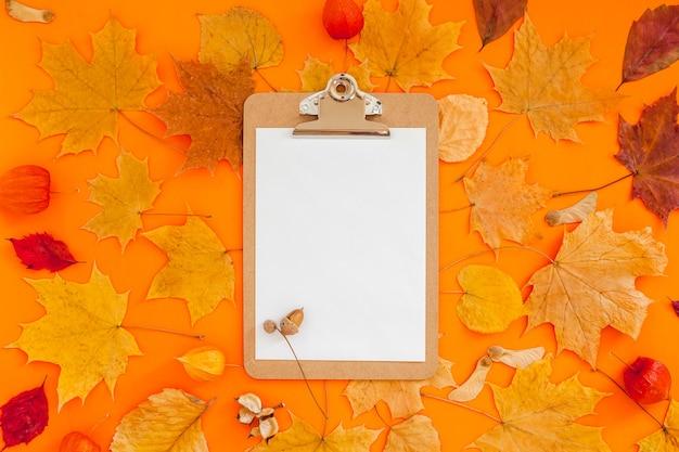大胆なオレンジ色の背景にクリップボードのモックアップと乾燥した葉を持つ秋のフラットレイ構成。創造的な秋、感謝祭、秋、ハロウィーンのコンセプト。上面図、コピースペース