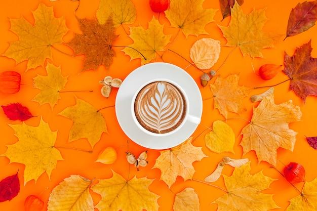 乾燥した葉とコーヒーカップの秋フラットレイアウト構成