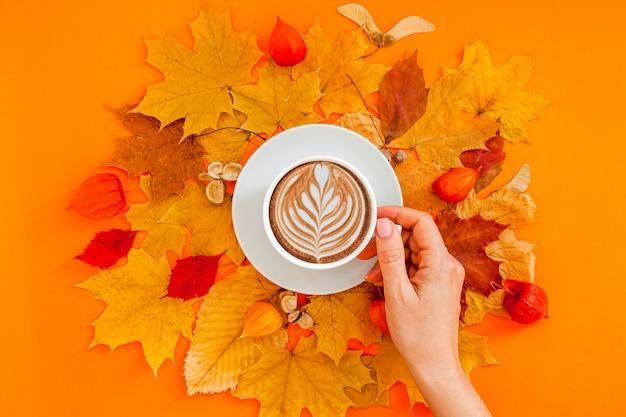 女性の手に乾燥した葉の花輪フレームとコーヒーラテカップと秋のフラットレイ構成