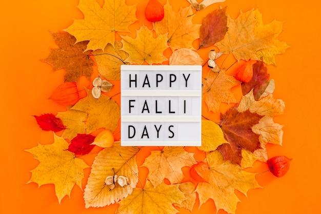 乾燥した葉の花輪フレームとライトボックスメッセージと秋のフラットレイ構成大胆なオレンジ色の背景に幸せな秋。創造的な秋の感謝祭の秋のハロウィーンのコンセプト。上面図、コピースペース