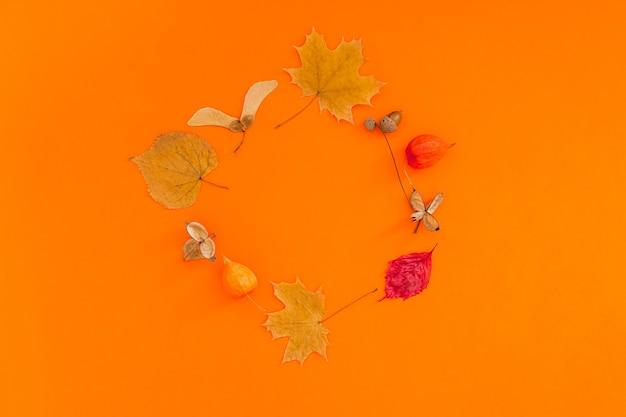 大胆なオレンジ色の背景に乾燥した葉の花輪フレームと秋のフラットレイ構成。創造的な秋、感謝祭、秋、ハロウィーンのコンセプト。上面図、コピースペース