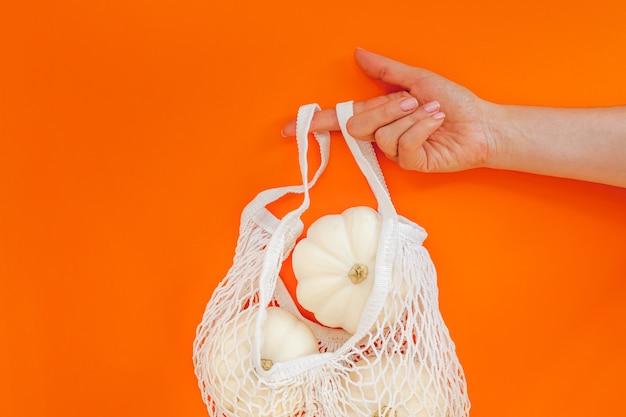 大胆なオレンジ色の背景にメッシュのショッピングバッグに白いカボチャと秋のフラットレイ構成。ゼロウェイストスタイルの創造的な秋、感謝祭、秋、ハロウィーンのコンセプト。上面図、コピースペース