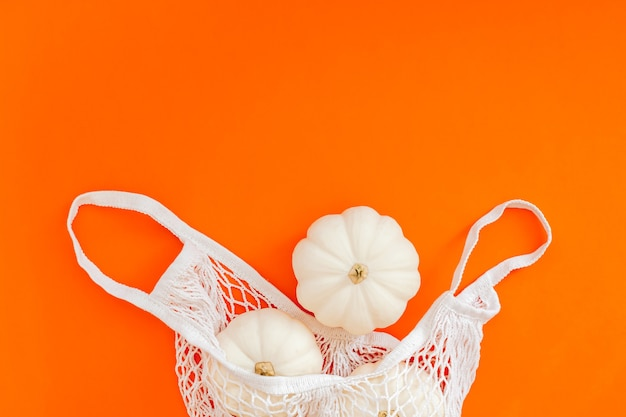 Autumn flat lay composition with white pumpkins in mesh shopping bag on bold orange color background.