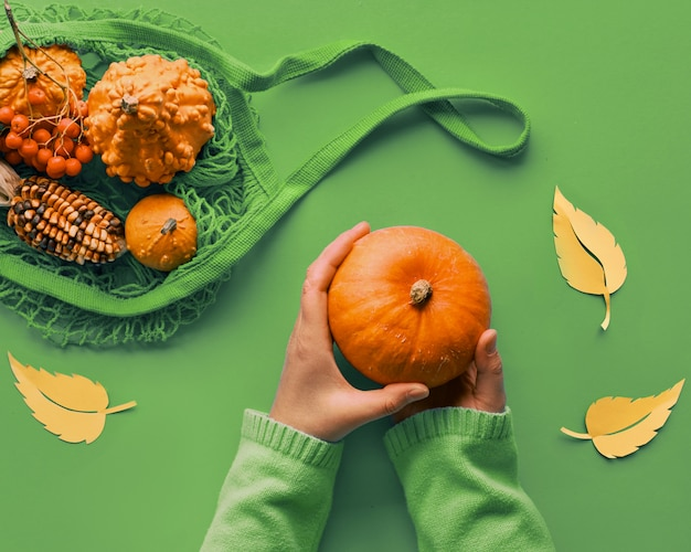 Autumn flat lay in green and orange with female hands holding pumpkin and string bag with more pumpkins