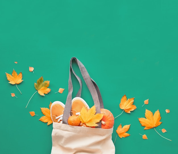 Autumn flat lay on light green background, text space. orange pumpkins and canvas shoes in beige eco friendly canvas bag and natural maple leaves.