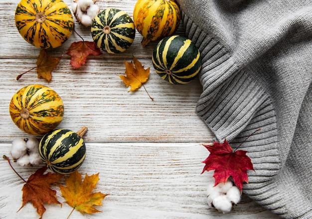 葉、カボチャ、灰色のスカーフの秋のフラットレイ