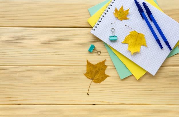 明るい木製の背景に学校やオフィスの文房具の秋のフラットレイ。テキスト用のスペース。