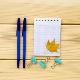 明るい木製の背景に学校やオフィスの文房具の秋のフラットレイ。