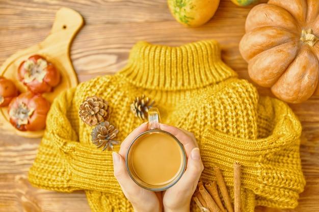 秋のフラットレイパンプキンコーヒーの紅葉とホットドリンクのニットセーターカップを手に秋のホリッド...