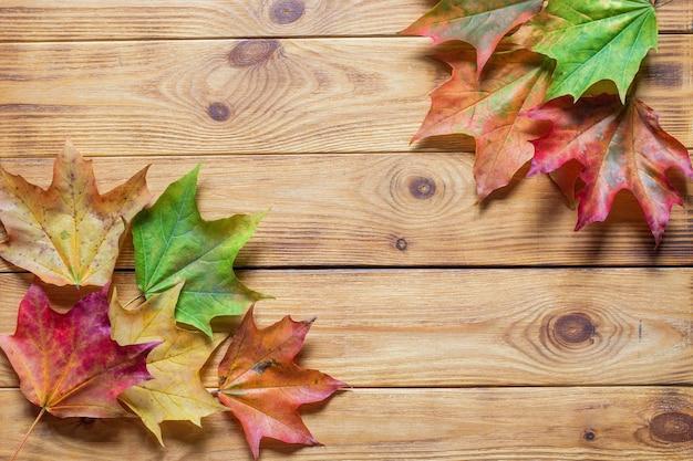 Осенняя квартира лежала с красочными опавшими листьями на деревянных фоне.