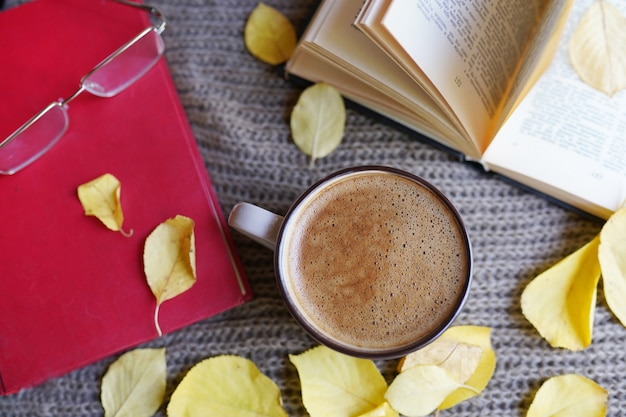 Autumn flat lay with cup of coffee, books and yellow leaves