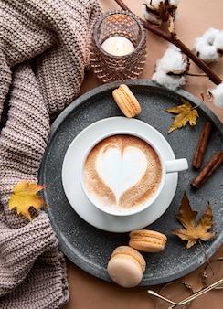Осенняя плоская кладка с чашкой кофе, теплым пледом, декоративными полосатыми тыквами, свечами и осенними листьями