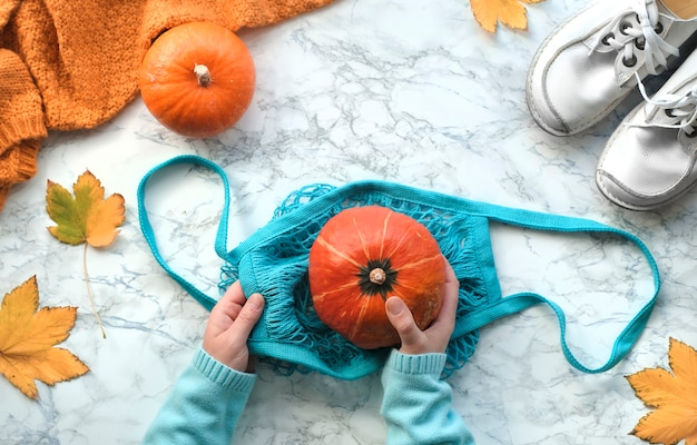 Autumn flat lay with female hands putting orange pumpkin into turquoise string bag