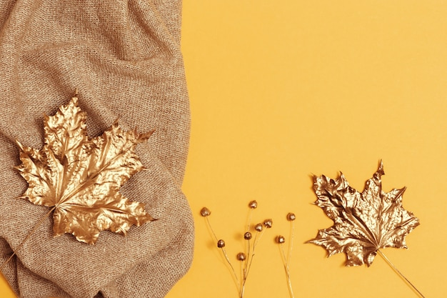 가 평면 니트 모직 베이 지 컬러 스카프, 노란 종이 바탕에 단풍 나무의 황금 건조 잎 누워. 패션 가을 옷. 복사 공간이있는 상위 뷰.