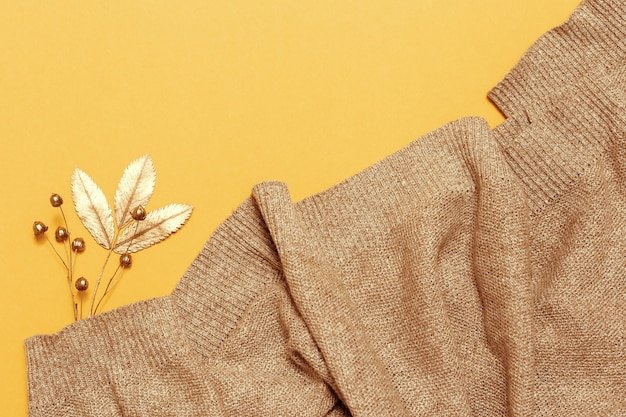 Autumn flat lay with knitted woolen beige colored scarf, golden dry leaves of rowan on yellow paper background.