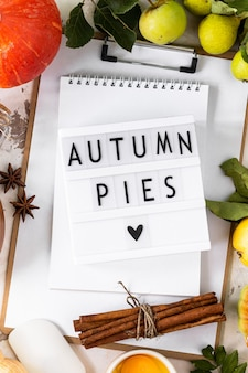 Autumn flat lay with lightbox with the phrase autumn pies. top view. food ingredients for making autumn pumpkin pie on a white stone background.
