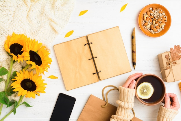 Autumn flat lay with notebook tea with female hands phone nuts gift on table