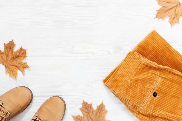 秋のフラットは、コピースペースを持つ白いウッドの背景にオレンジ色の靴とファッションオレンジのコーデュロイパンツで横たわっていた。女性の快適な服には、黄色のカエデの葉が飾られています。上面図。