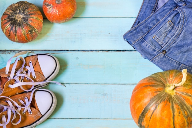 Autumn flat lay with pumpkin jeans sneakers sweatshirt
