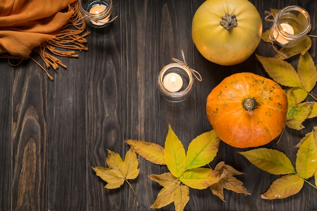 Autumn flat lay with pumpkins, yellow autumn leaves and candles