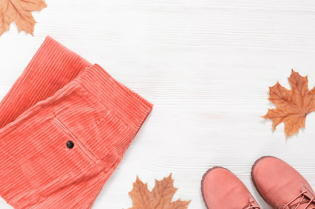 Autumn flat lay with shoes and fashion corduroy pants with yellow maple leaves