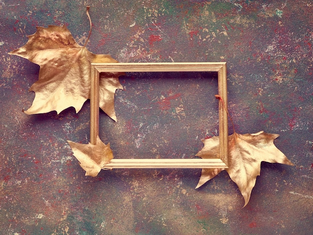 Autumn flat lay with sycamore leaves painted gold and copy-space in golden frame on dark textured canvas