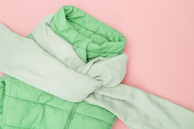 Autumn flat lay with warm clothing trend color on pink background. bright fashion clothes for womans. down jacket neo mint colored, textile wide scarf. top view. flat lay.
