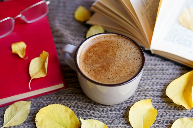 Autumn flatlay with cup of coffee, books, glasses, yellow leaves and books on scarf