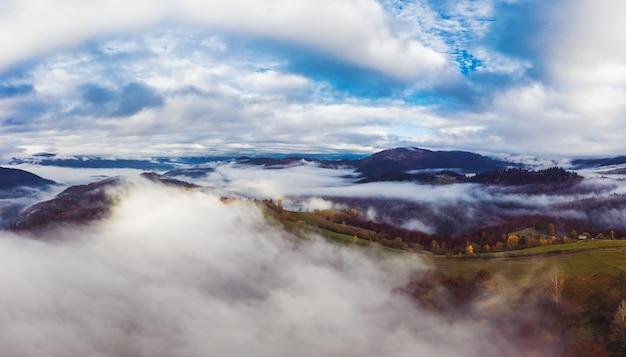 Осенний полет через голубое небо в карпатских осенних горах