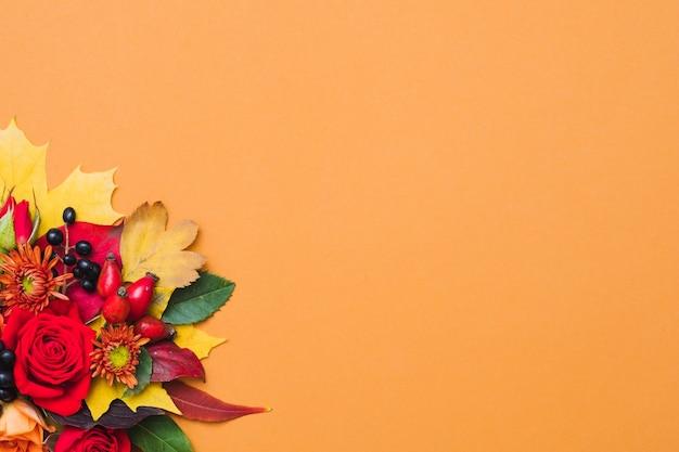Осенняя цветочная композиция осенние ягоды, разноцветные листья и красные розы на оранжевом