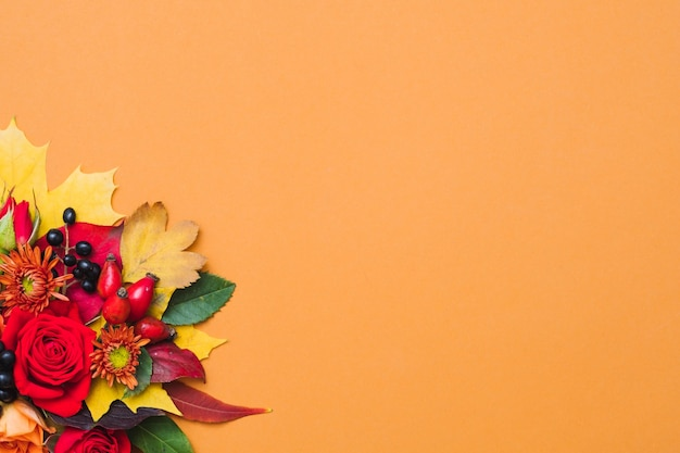 Autumn floral arrangement fall berries, colorful leaves and red roses on orange
