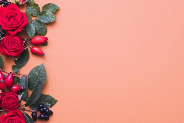 Осенняя цветочная композиция красные и черные осенние ягоды, зеленые листья и розы на пастельном коралловом фоне