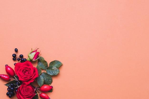 Осенняя цветочная композиция красные и черные осенние ягоды, зеленые листья и розы на пастельных кораллах