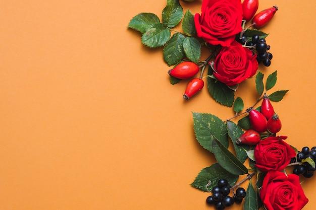 秋のフラワーアレンジメント赤い秋のベリー、緑の葉、オレンジ色のバラ
