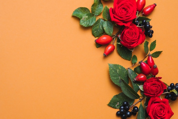 Autumn floral arrangement red fall berries, green leaves and roses on orange